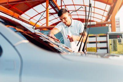 Man rubbing vehicle with car polish